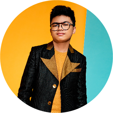 Joey Alexander stands, wearing a black jean jacket with yellow lapels, agains a half yellow, half teal background