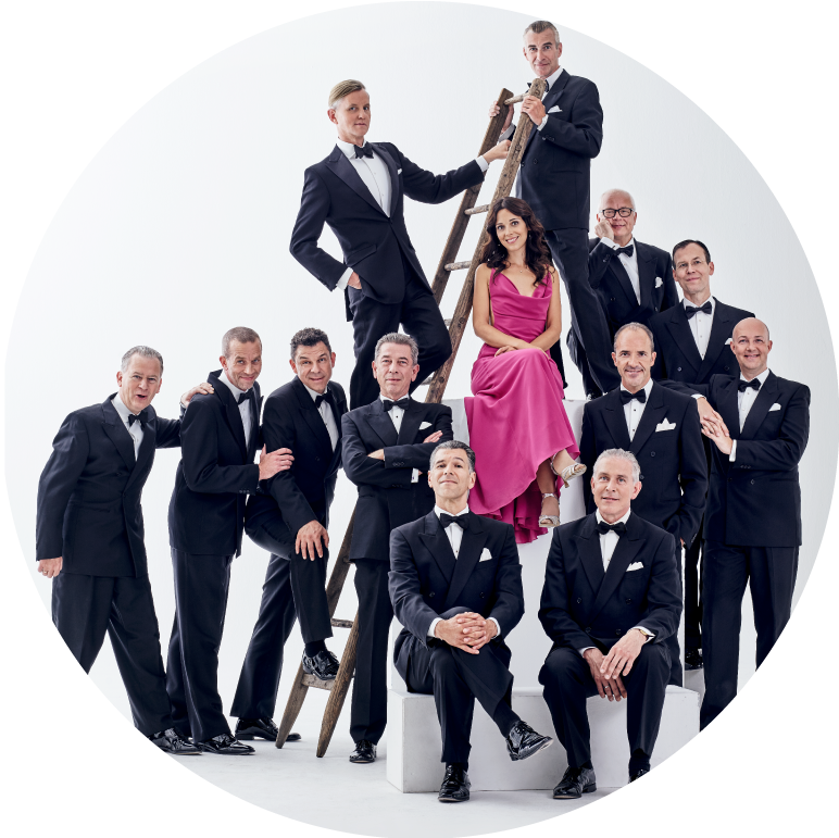 Max Raabe & Palast Orchestra formal group photo in white studio with Max Raabe halfway up a ladder