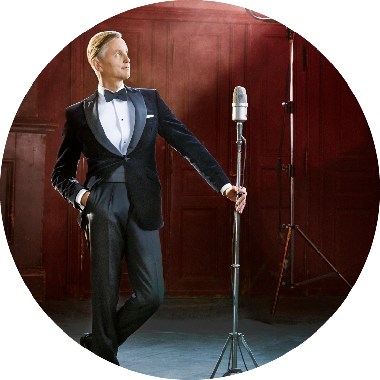 Max Raabe dressed in a tuxedo leaning against mic stand on stage in front of a red wall