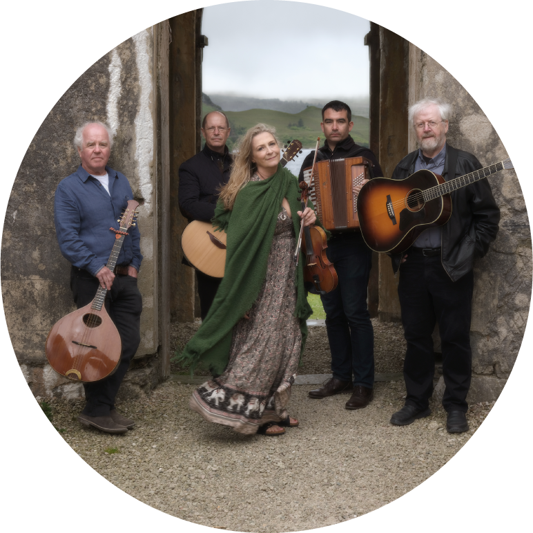 Altan stands holding their instruments in the doorway of what looks like an ancient castle or ruin in the Irish countryside