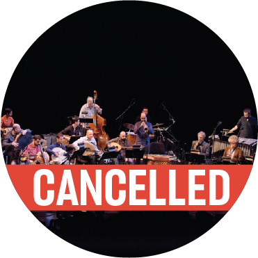 """The full 17-piece band performs on stage in front of a live audience against a black backdrop. Amir ElSaffar stands to play the trumpet with a poppy banner that reads """"cancelled"""" over the image"""