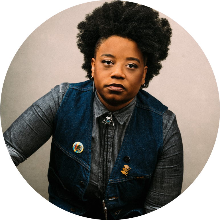 A circular image of Amythyst Kiah from the waist up. Amythyst is dark-skinned and has short black hair. She wears a blue denim vest over a gray long-sleeved button-up shirt. On the vest are 2 pins: a round colorful pin on her right side and 1 with 3 gold hands giving peace signs on the other side. Around her collar is silver bolo tie with a blue eye in a triangle.