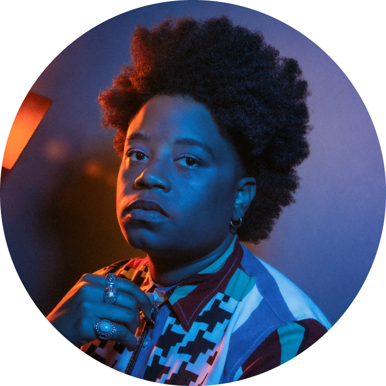 A circular image of Amythyst Kiah from the shoulders up. She is dark-skinned with short black hair. She is wearing a button-up shirt with blue white, blue, and red stripes and black and white houndstooth. She adjusts a bolo tie with her hand. She wears three silver rings and small hoop earrings