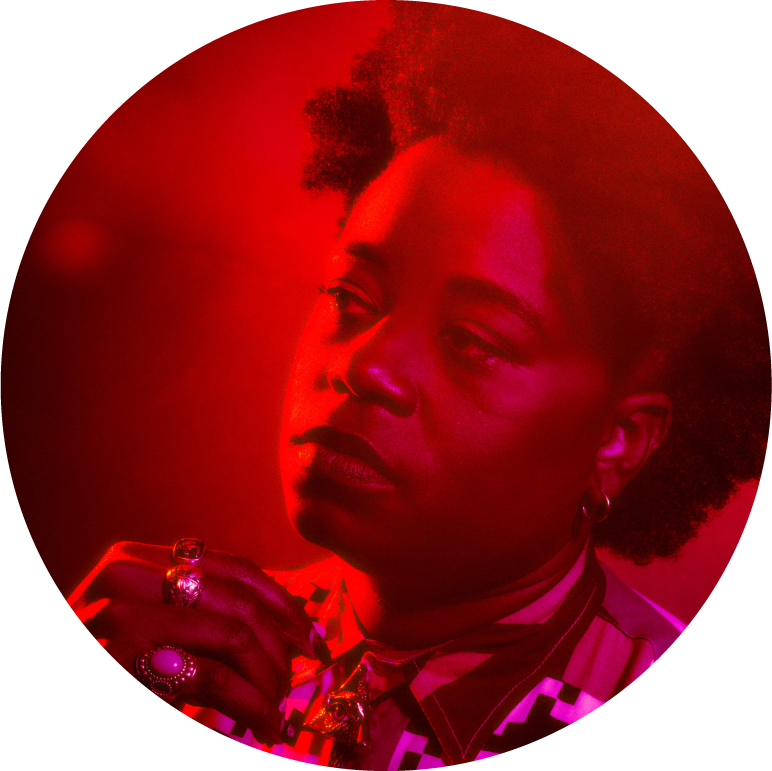 A circular image of Amythyst Kiah from the shoulders up. She is covered in red light. She adjust a bio tie and looks off to the side.