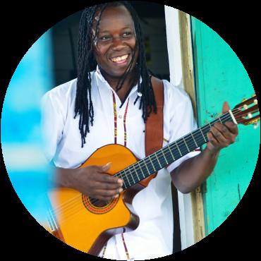 Aurelio smiles and holds guitar in doorway