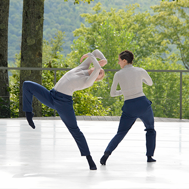 Boston Dance Theater Two dancers in grey sweater and jeans dancing on white wooden floor in front of some trees