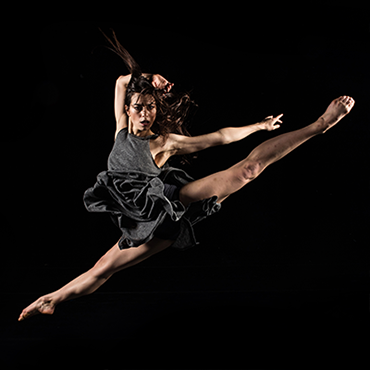 Bodytraffic female dancer jumping mid-air looking towards camera with black background