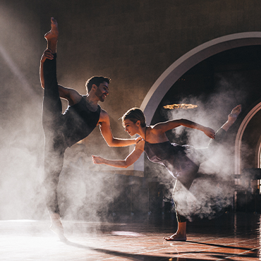 Bodytraffic male and female dancers with their legs up in the air in a room with arches and smoky background