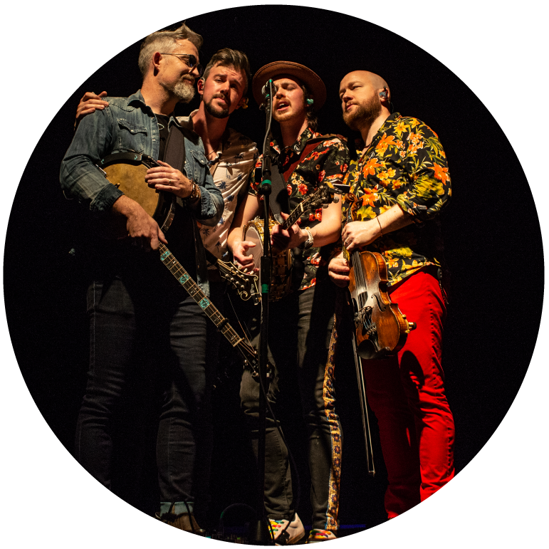 The four members of We Banjo 3 in front of a black background sing into a microphone