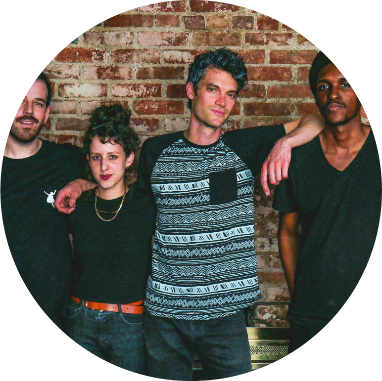 The four members of Billy Wylder stand in front of a brick wall. They are all wearing black-short sleeved shirts and dark blue jeans. The first three people from the left are light-skinned and the fourth person has dark skin.