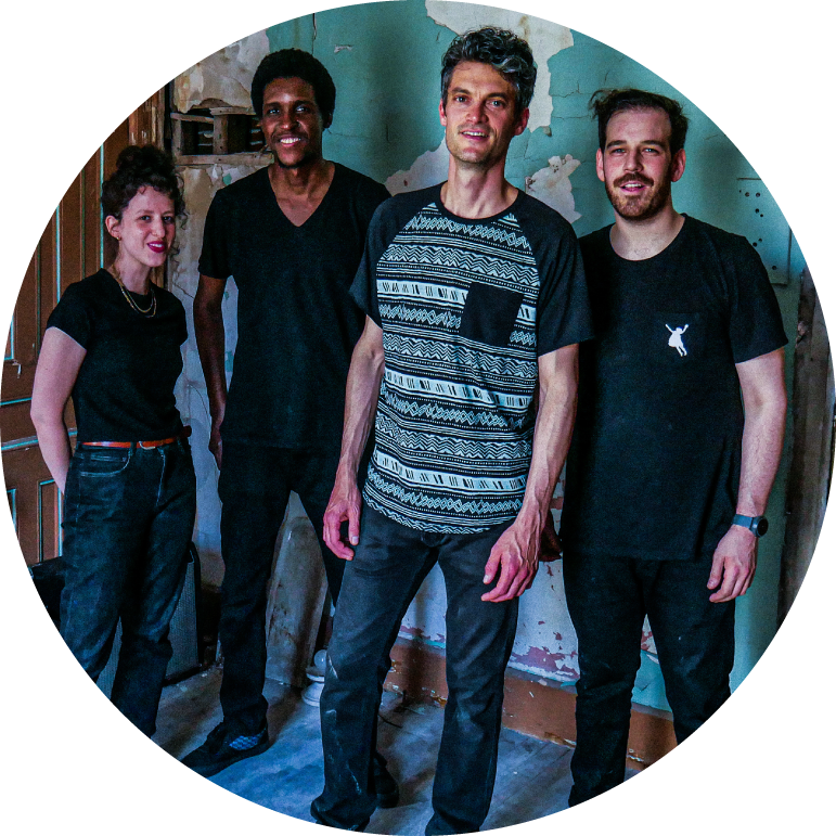 The four members of Billy Wylder stand in front of a light blue wall. They are all wearing black-short sleeved shirts and dark blue jeans.