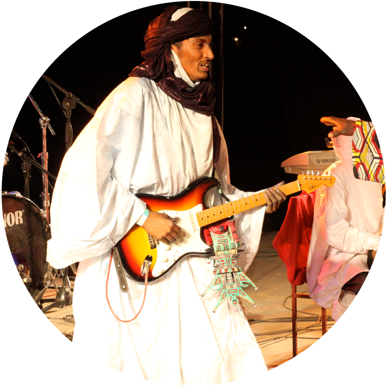 Bombino wears a white robe and brown turban while playing the electric guitar.