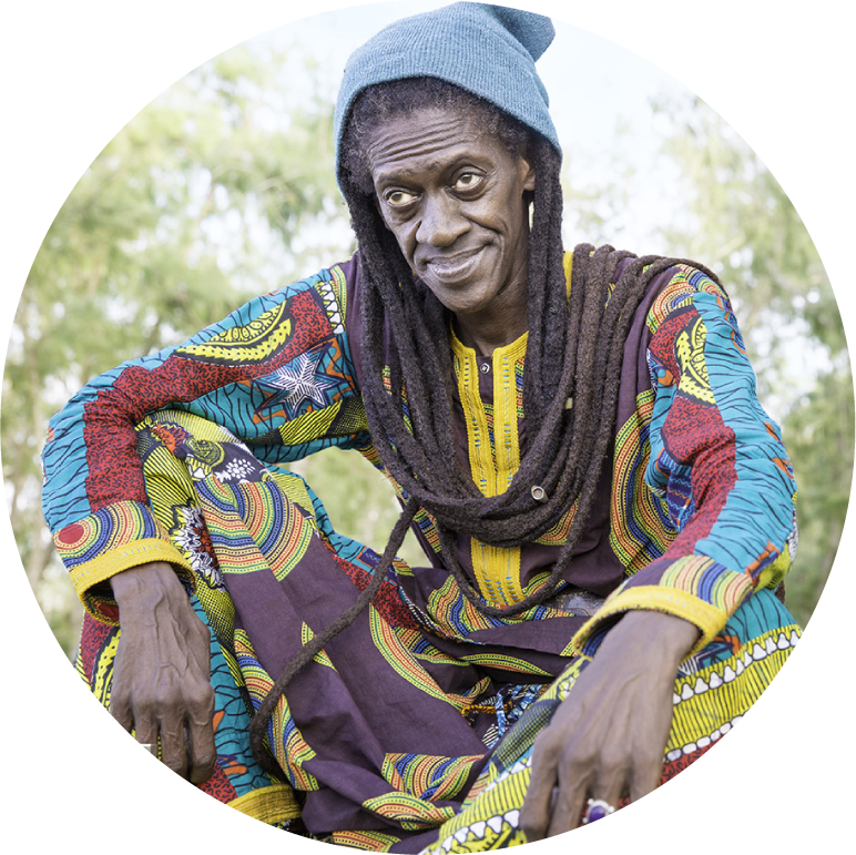 Cheikh Lo in colorful attire sitting and gazing thoughtfully past the camera beneath trees