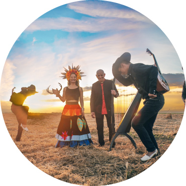The sun sets in the background of a field of straw, with musicians in black hats dancing around a female holding an animal horn