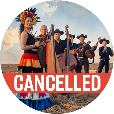 "A woman in a back top, brightly colored skirt, wearing a tiara of brightly colored flowers and feathers holding animal horns, with the rest of the band wearing black hats holding their instruments stand behind her with a poppy colored ""cancelled"" banner over the image"