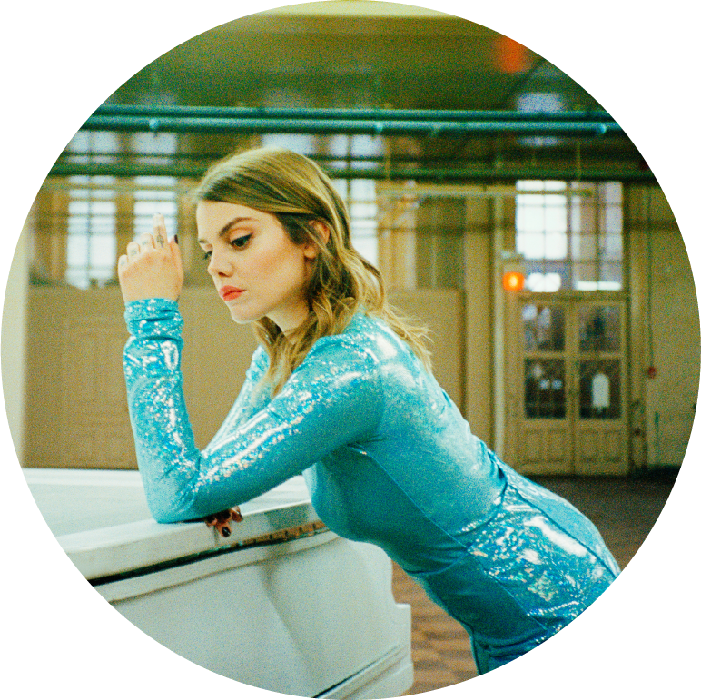 Coeur de Pirate stands in a long sleeved blue sparkly dress leaning with her left arm on a white piano. She looks down at the piano