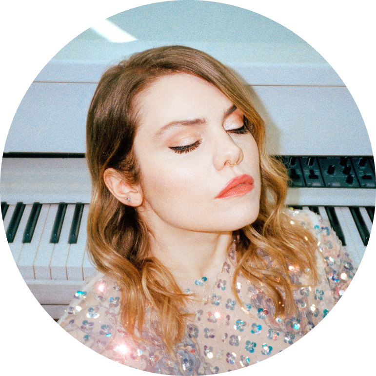 Close up of Coeur de Pirate with her eyes closed with pink lipstick and her dark blonde hair down in waves across her shoulders with a piano behind her