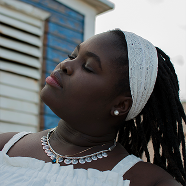 Dayme Arocena facing sky with eyes closed wearing white headband in front of a blue house