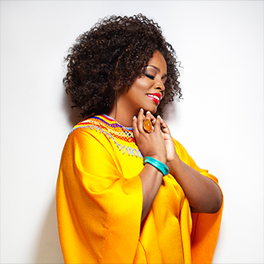 Dianne Reeves wearing yellow robe smiling with eyes closed looking away from camera