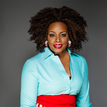 Dianne Reeves in blue blouse looking into camera with grey backdrop