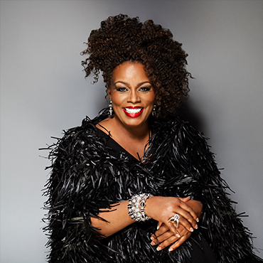 Dianne Reeves in black outfit smiling in to camera with grey backdrop