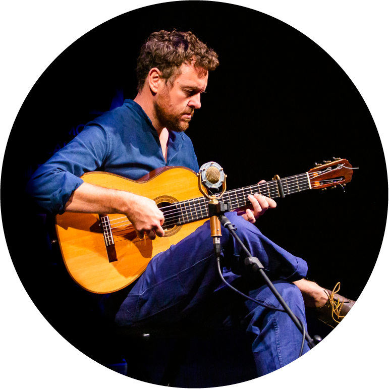 Derek Gripper wearing blue pants and a blue button up top, playing the guitar with his right leg crossed over the left
