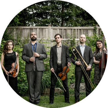 Ezekiel's Wheels Klezmer Band stands in backyard holding instruments