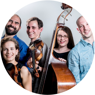 Ezekiel's Wheels Klezmer Band stands in front of white backdrop smiling and holding instruments