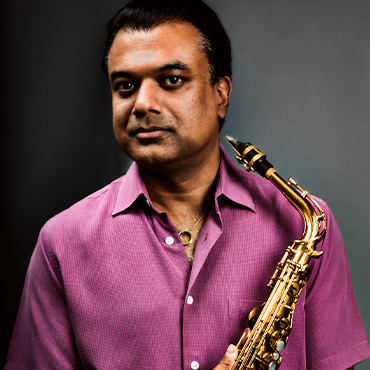 Rudresh Mahanthappa in pink shirt holding saxophone while giving the camera a cool gaze in front of a grey background