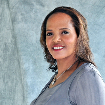 Terri Lyne Carrington in grey blouse turning toward camera while smiling in front of a grey backdrop