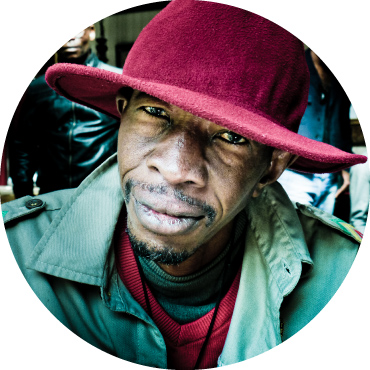 Lead singer in a green coat with a cranberry colored hat looking directly into the camera.