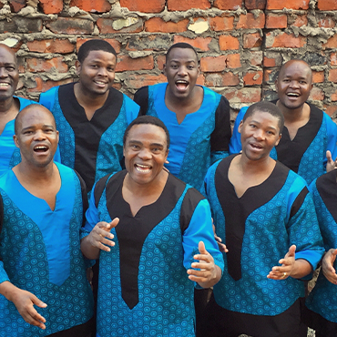 Ladysmith Black Mambazo dressed in light blue singing in formation in front of brick wall
