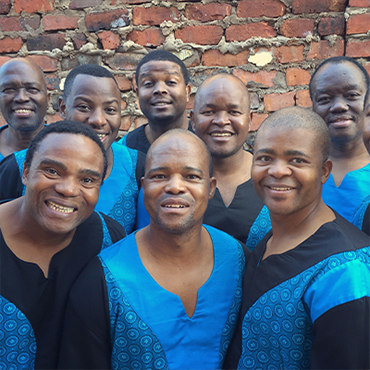 Members of Ladysmith Black Mambazo stand in front of a brick wall wearing matching blue and black shirts with smiles on their faces
