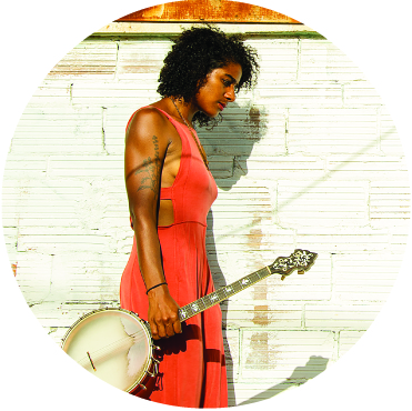 Leyla McCalla in a red dress holding her banjo walking along a white brick wall