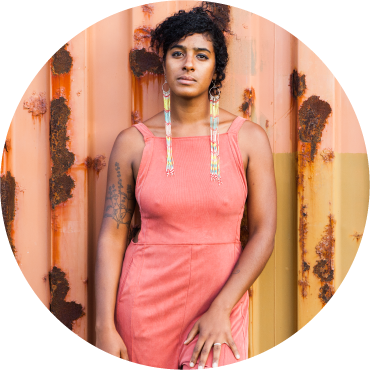 Leyla McCalla stands in front of a pinkish rusted storage container, wearing a coral dress and long beaded earrings. She's looking directly at the camera with her hair piled into a knot on top of her head and with one arm by her side and one hand resting on her thigh