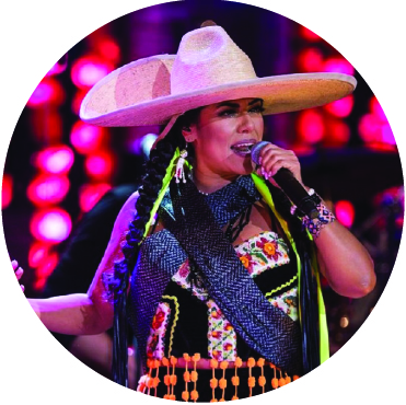 Lila Downs performing live wearing a large hat and colorful outfit