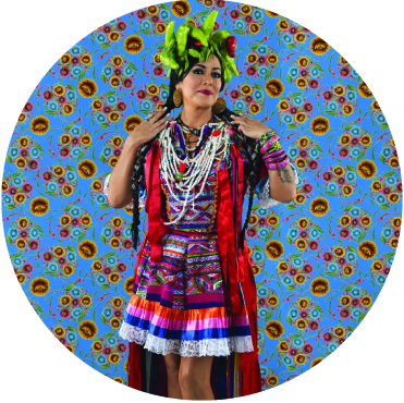 Lila Downs dancing with a crown of peppers on her head against a blue backdrop