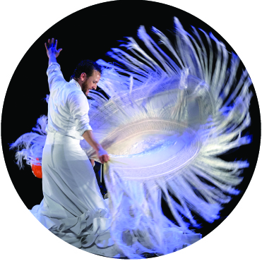 Manuel Linan twirling a fringe lined white flamenco shawl in a dramatic fashion