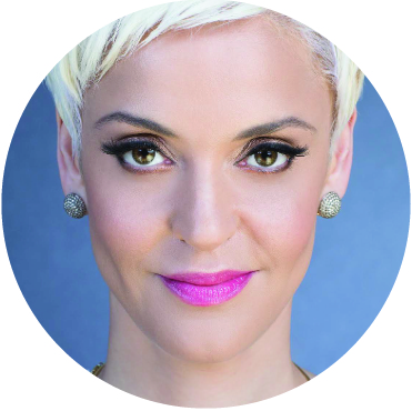Close up photo of Mariza, smiling, looking directly at the camera with pink lipstick and a blue background