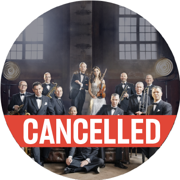 "Max Raabe & Palast Orchestra formal group photo in warehouse in front of brick wall and windows with a poppy colored ""cancelled"" banner over the image"