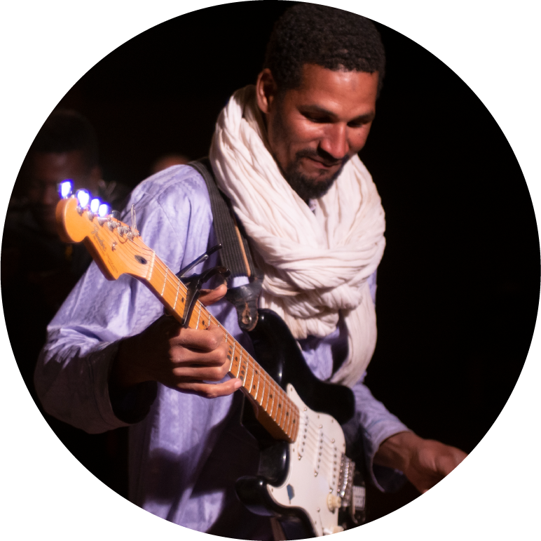Mdou wears a lilac colored long sleeve shirt with a white scarf wrapped around his neck. He plays his black and white guitar.