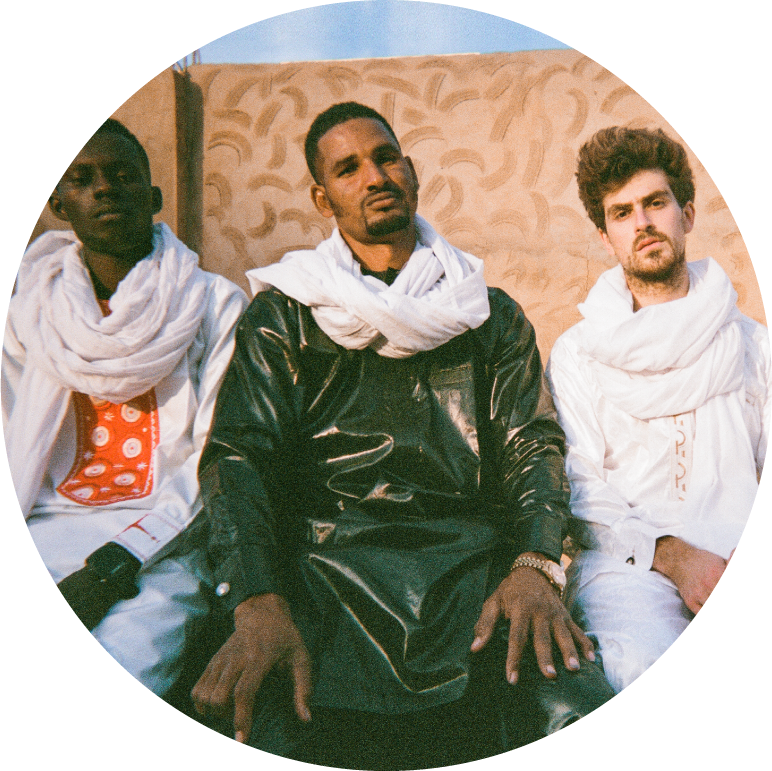 Mdou Moctar sits in a green shirt with white scar wrapped around his neck in front of a sand colored wall. To his left and right sit his band mates, both wearing white scarfs wrapped around their necks.