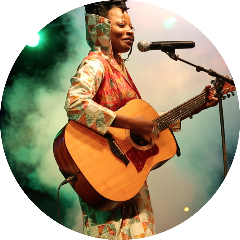 Natu Camara stands in front of a green background and white fog, while playing an acoustic guitar and singing into a microphone. She has dark skin and black hair that is in an updo. She wears a white, green, and orange jacket.