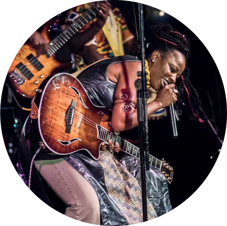 Natu Camara has dark skin with black and red dreadlocks. She wears a black long leather tank top, gray jeans, small stud earrings, and a spiral bracelet on her upper arm. She has a guitar on and bends over and sings into a microphone.