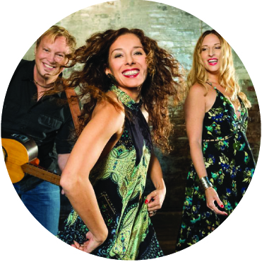 Three members of the group Newpoli dancing, looking at the camera, including singers Carmen Marsico and Angela Rossi