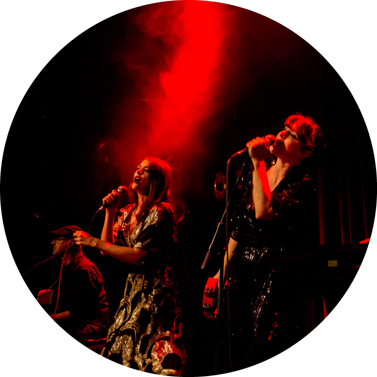 The two singers of Nouvelle Vague stand on stage with red light radiating from the top of the photo. They both hold microphones up to their faces.