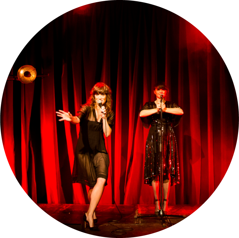 The two singers of Nouvelle Vague stand on a stage with a curtain lit by red light behind them. One singer dances towards the camera holding a microphone with her left hand with her right hand outstretched, the other stands in the background with both hands gripping the microphone stand.