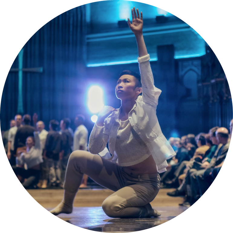 One dancer kneels with their left knee on the ground and their right knee bent. Their left hand is in the air. Dancer wears khaki pants and a white top with an open white button up.