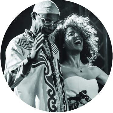 Black and white photo of Omar Sosa and Yilian Canizares performing. Both are smiling but she appears to also be singing