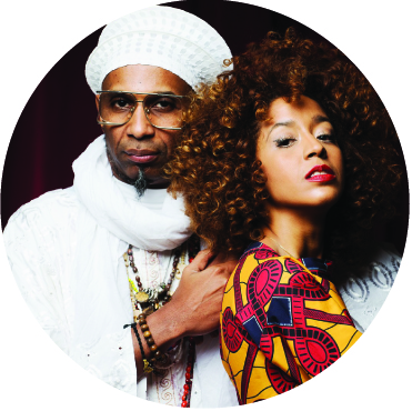Yilian Canizares standing with her back to Omar Sosa and his hand is on her shoulder. He's wearing all white and she's in a colorful pink and yellow top